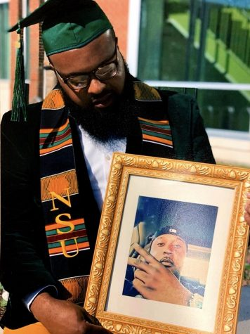 "Antonio Howell holds a picture of his twin brother after graduation. His brother passed away on May 9th, 2014. ""I knew he was smiling down proud of my accomplishments"" said Howell."